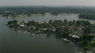 AX73_052 - 5K stock footage aerial video of row houses and riverfront homes with docks by Dark Head Creek and Middle River in Middle River, Maryland