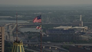 AX73_089 - 5K stock footage aerial video orbiting American and Maryland flags, Downtown Baltimore, Maryland