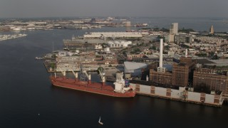 AX73_095 - 5K stock footage aerial video of a cargo ship at Domino Sugar Factory, waterfront factory buildings, Baltimore, Maryland