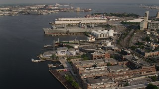 AX73_096 - 5K stock footage aerial video of waterfront factory buildings and docked ships in Baltimore, Maryland
