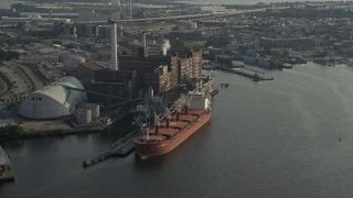 AX73_101 - 5K stock footage aerial video of a cargo ship docked by the Domino Sugar Factory, Baltimore, Maryland