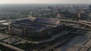 AX73_113 - 5K stock footage aerial video orbiting M&T Bank Stadium to reveal Downtown Baltimore skyscrapers, Maryland