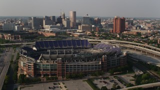 AX73_114 - 5K stock footage aerial video orbiting M&T Bank Stadium with Downtown Baltimore skyscrapers in the background, Maryland