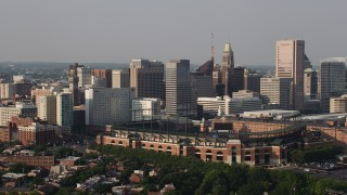 AX73_115 - 5K stock footage aerial video of Oriole Park baseball stadium and Downtown Baltimore skyscrapers, Maryland