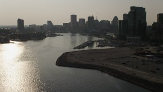 AX73_127 - 5K stock footage aerial video following Patapsco River toward Inner Harbor and the Downtown Baltimore skyline, Maryland