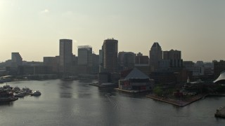 AX73_128E - 5K stock footage aerial video flying low toward Inner Harbor and National Aquarium in Downtown Baltimore, Maryland