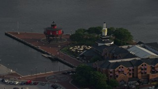 AX73_135 - 5K stock footage aerial video of Pier 5 Hotel Complex and the Seven Foot Knoll Lighthouse, Downtown Baltimore, Maryland