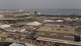 AX73_142 - 5K stock footage aerial video of warehouses and salt piles near a train yard and Interstate 95 in Baltimore, Maryland