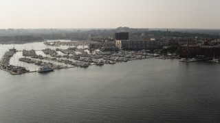 AX73_144 - 5K stock footage aerial video of Baltimore Marine Center and office buildings by the Patapsco River in Maryland