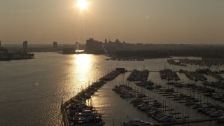 AX73_148 - 5K stock footage aerial video flying over Baltimore Marine Center to approach Downtown Baltimore skyline at sunset, Maryland