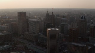 AX73_153 - 5K stock footage aerial video of Downtown Baltimore skyscrapers and office tower at sunset, Maryland