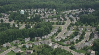 AX74_007 - 5K stock footage aerial video flying by a suburban neighborhood in Manassas, Virginia
