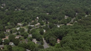 AX74_011 - 5K stock footage aerial video flying by suburban homes and lush green trees in Clifton, Virginia
