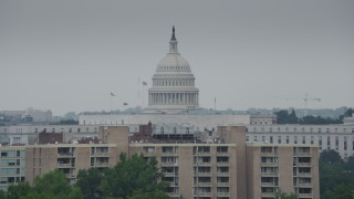 AX74_065 - 5K stock footage aerial video of the United States Capitol Dome seen while flying by a smoke stack in Washington DC
