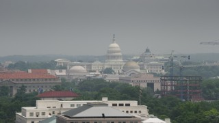 AX74_077 - 5K stock footage aerial video of the United States Capitol seen over Smithsonian Museum domes in Washington DC