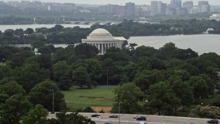 AX74_093 - 5K stock footage aerial video of the Jefferson Memorial partially hidden by trees in West Potomac Park in Washington DC