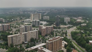 AX74_123 - 5K stock footage aerial video flying over apartment complexes, hotel, and office buildings to approach row houses in Alexandria, Virginia