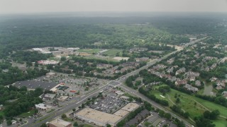 AX74_127 - 5K stock footage aerial video flying over shops and Little River Turnpike to approach a high school in Alexandria, Virginia