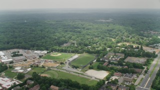 AX74_128 - 5K stock footage aerial video flying over high school to approach a suburban neighborhood in Alexandria, Virginia