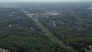 AX74_135 - 5K stock footage aerial video of rows of power lines on a green strip between trees and suburbs in Burke, Virginia