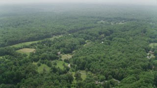 AX74_142 - 5K stock footage aerial video flying over upscale homes in a green forest in Fairfax Station, Virginia