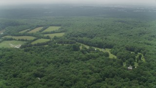 AX74_145 - 5K stock footage aerial video flying over forest to approach clearings in Clifton, Virginia