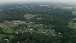 AX74_146 - 5K stock footage aerial video flying over forest to approach rural homes in Manassas, Virginia