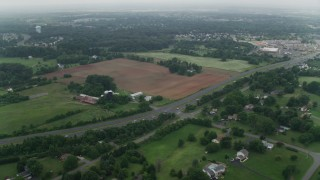 AX74_148 - 5K stock footage aerial video flying over rural homes and farm fields around Prince William Parkway in Manassas, Virginia