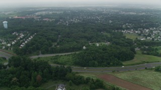 AX74_149 - 5K stock footage aerial video flying over trees to approach a church and elementary school by suburban homes in Manassas, Virginia