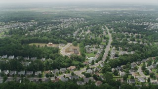 AX74_150 - 5K stock footage aerial video flying over ponds to approach Prince William County Fairgrounds by suburban homes in Manassas, Virginia