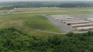 AX74_153 - 5K stock footage aerial video approaching hangars and runway at Manassas Regional Airport, Virginia