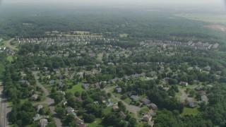 AX75_001 - 5K stock footage aerial video flying by suburban neighborhoods, Manassas, Virginia