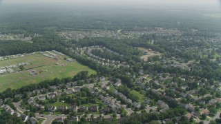 AX75_002 - 5K stock footage aerial video flying by neighborhoods in Manassas, Virginia to reveal Prince William County Fairgrounds
