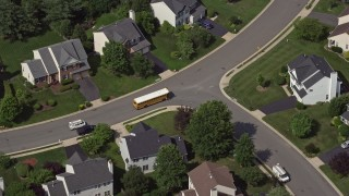 AX75_004 - 5K stock footage aerial video tracking a school bus in a suburban neighborhood in Manassas, Virginia