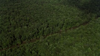 AX75_007 - 5K stock footage aerial video tilting to reveal the Bull Run River through forest in Clifton, Virginia