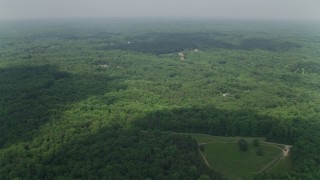 AX75_008 - 5K stock footage aerial video flying over forest, approaching upscale homes, Clifton, Virginia