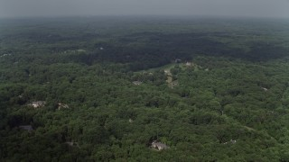 AX75_008E - 5K stock footage aerial video flying over forest, approaching upscale homes, Clifton, Virginia