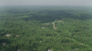 AX75_009 - 5K stock footage aerial video flying over forest, approaching a clearing with upscale homes, Clifton, Virginia