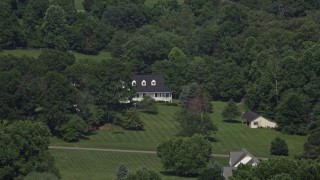 AX75_012 - 5K stock footage aerial video of an isolated home partially hidden by trees in Clifton, Virginia