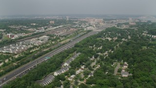 AX75_033 - 5K stock footage aerial video flying by Interstate 95 between train yard and suburban homes in Alexandria, Virginia