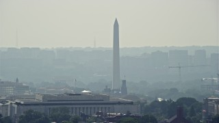 AX75_066 - 5K stock footage aerial video of the Washington Monument seen over rooftops in Washington DC