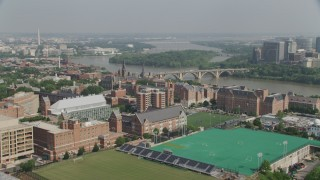 AX75_119 - 5K stock footage aerial video orbiting Georgetown University campus and reveal Washington Monument in Washington DC