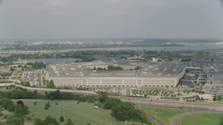 AX75_128 - 5K stock footage aerial video orbiting The Pentagon in Washington DC, with bridges over the Potomac in the background