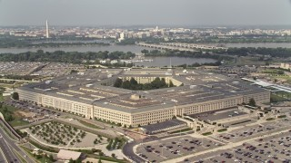 AX75_128E - 5K stock footage aerial video orbiting The Pentagon in Washington DC, with bridges over the Potomac in the background