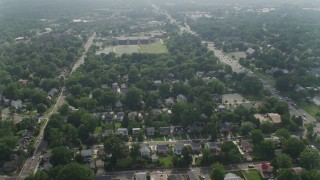 AX75_140 - 5K stock footage aerial video flying over suburban homes to approach an elementary school in Arlington, Virginia
