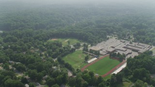 AX75_145 - 5K stock footage aerial video flying over Stuart High School beside Lake Barcroft in Falls Church, Virginia