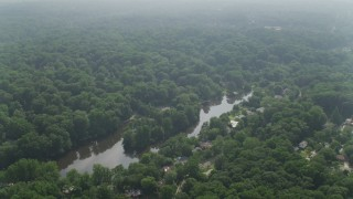 AX75_146 - 5K stock footage aerial video flying over Lake Barcroft and tree-covered suburbs in Falls Church, Virginia