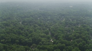 AX75_147 - 5K stock footage aerial video flying over suburban neighborhoods with Dense tree growth in Falls Church, Virginia