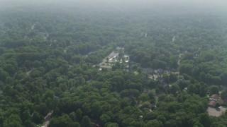 AX75_148 - 5K stock footage aerial video flying over tree-lined neighborhoods in Falls Church, Virginia