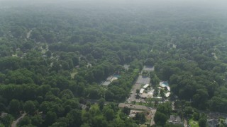 AX75_149 - 5K stock footage aerial video flying over residential neighborhoods with dense tree growth in Falls Church, Virginia